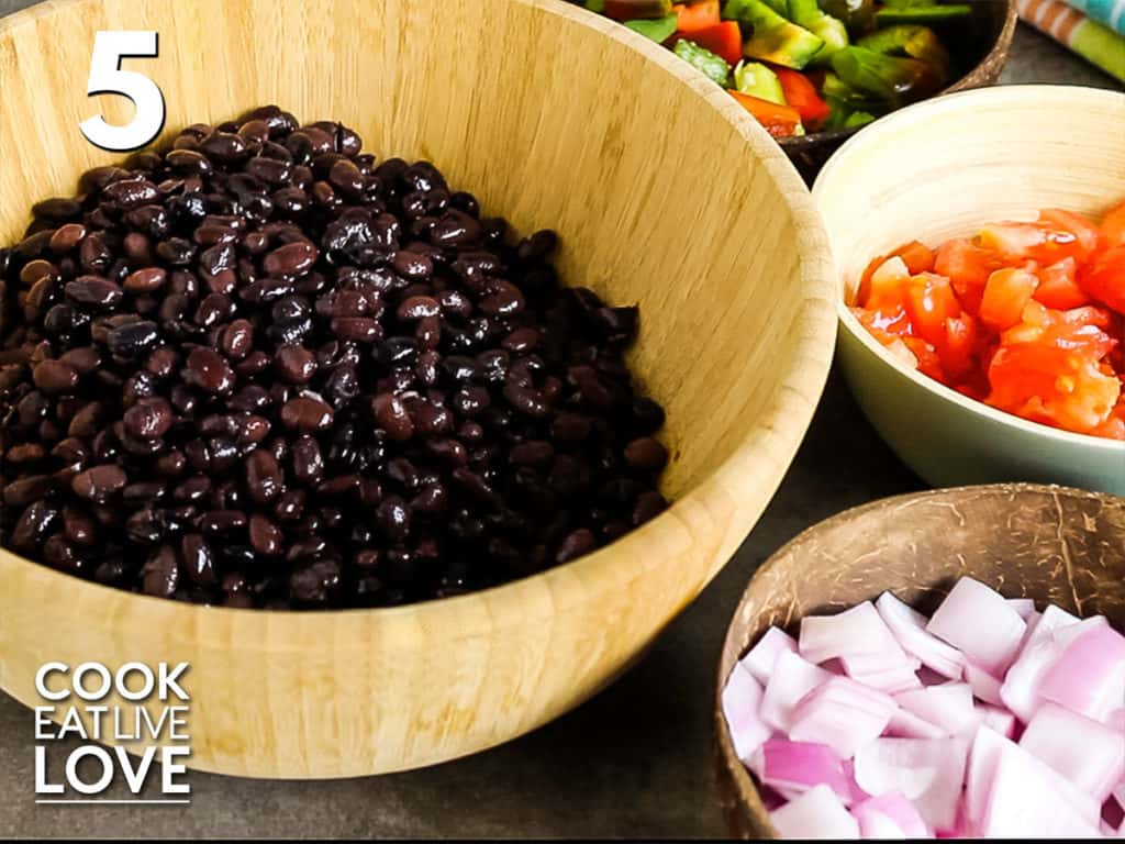 Wooden bowl filled with black beans on the right side are bowls of onions, tomatoes and bell pepper.