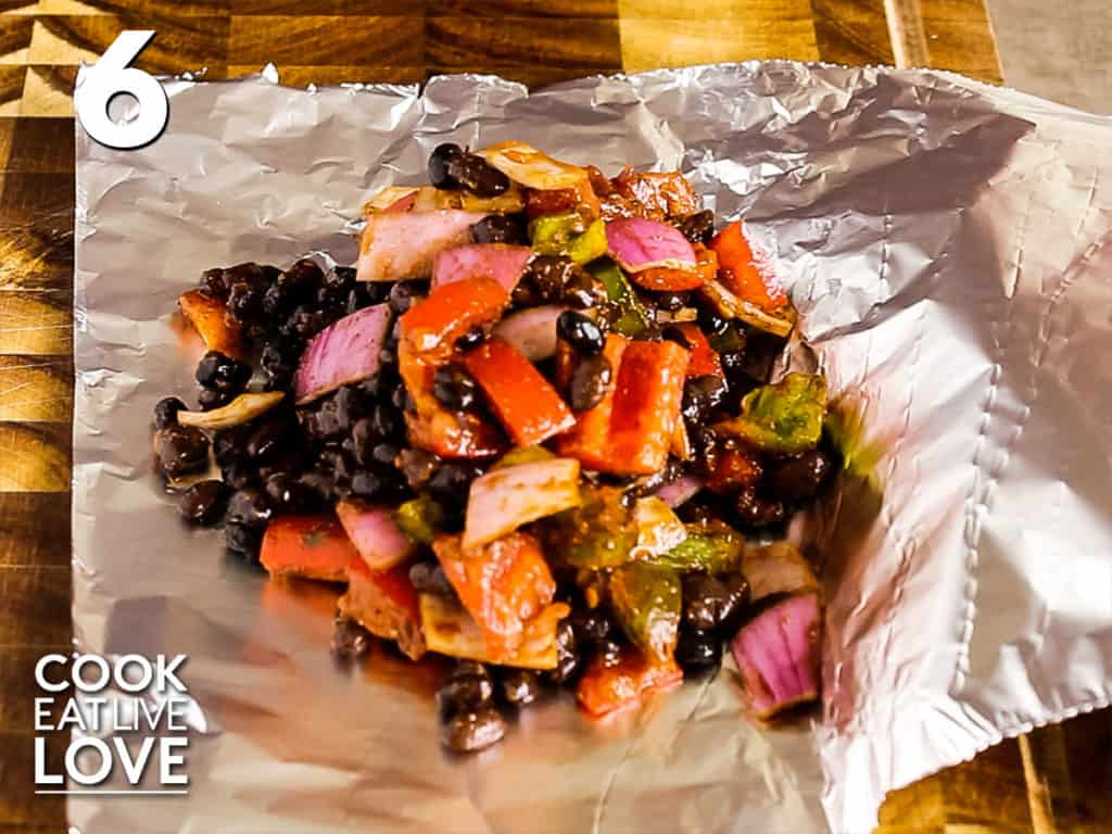 Piece of foil folded in half and one side is topped with black bean mixture.