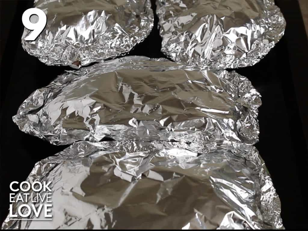 All the foil packets are piled up on a baking tray ready for the oven.