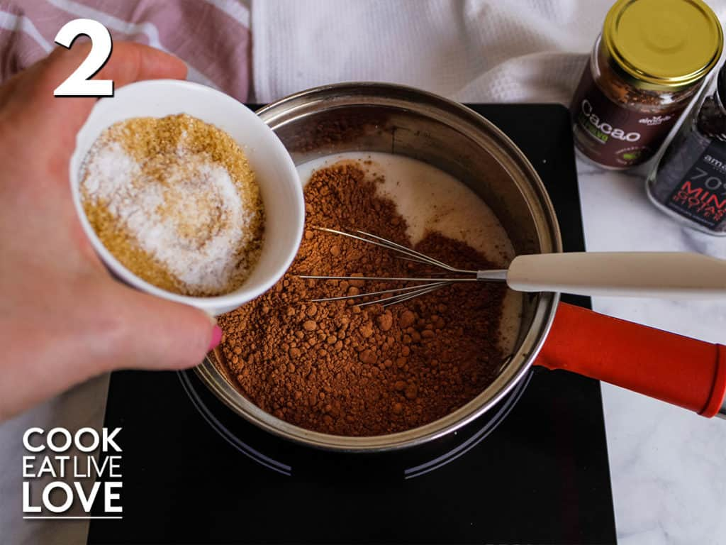 Saucepan with milk and cacao powder with a whisk inside.  A hand holds the sugar and salt about to be added to the pan.