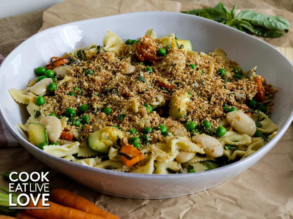 Pasta in white serving bowl with breadcrumb topping sitting on brown craft paper with fresh basil leaves and baby carrots on outside of bowl.