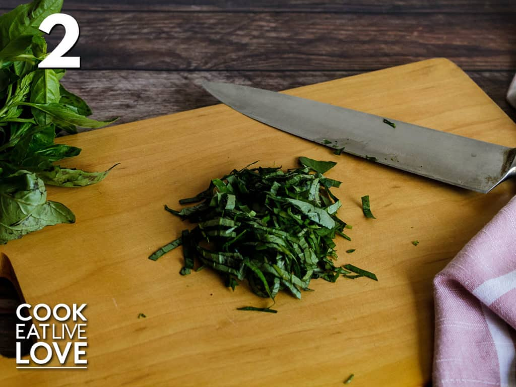 Fresh basil on cutting board, cut into small strips with knife to the side.
