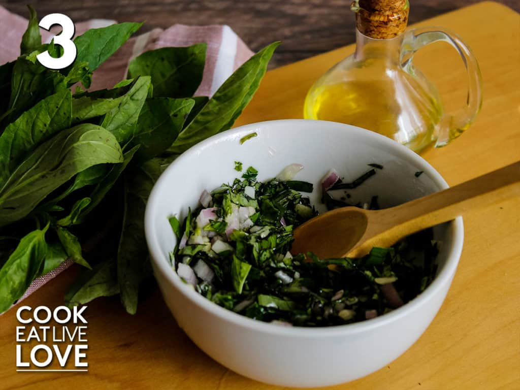 Basil is mixed with other ingredients in a bowl with a wooden spoon.  Above the bowl are fresh basil and a small jar of olive oil.