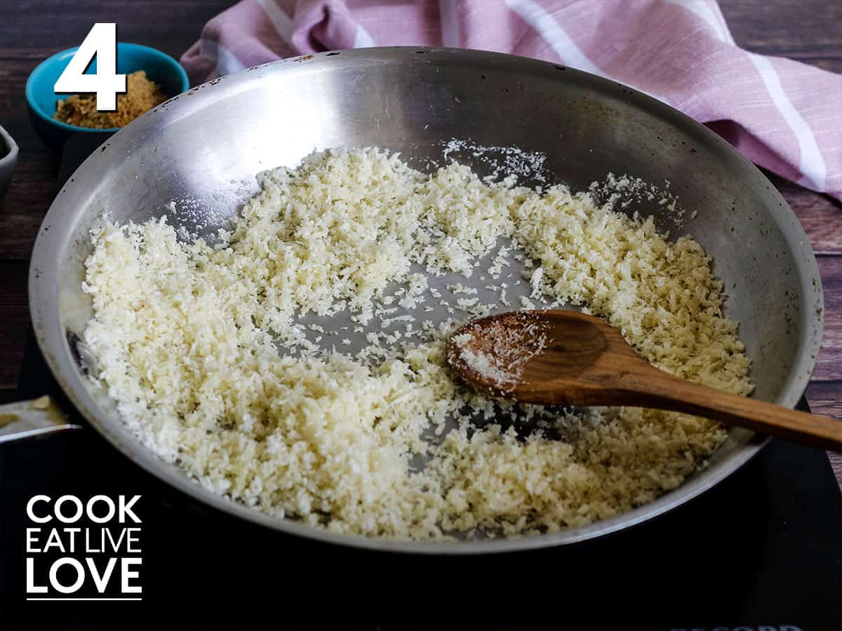 Panko is in saute pan at the start of cooking with wooden spoon to the side.