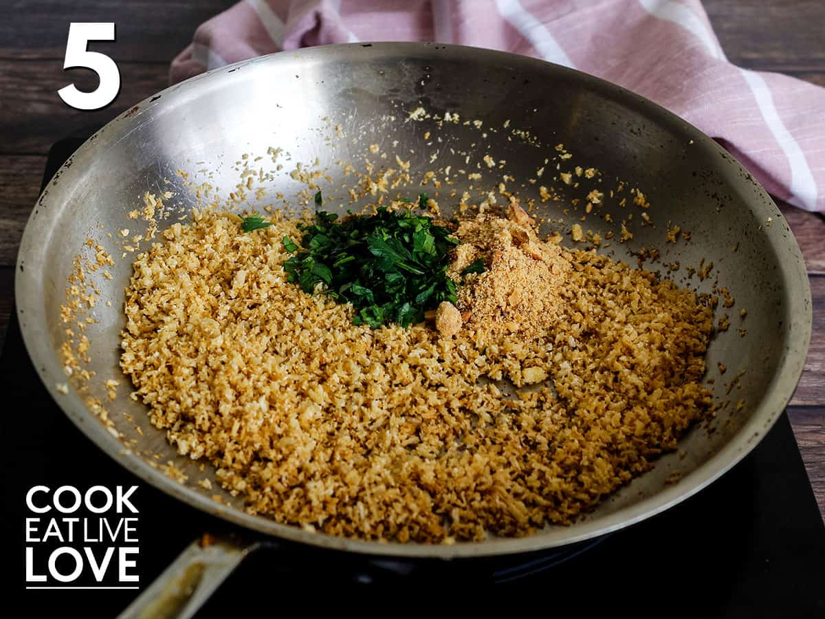 Panko in cooking pan is lightly tan after cooking with parsley added to the pan.
