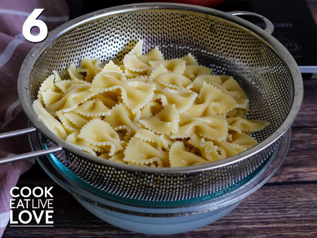 Bowtie pasta is in a strainer set over glass bowl to catch the pasta cooking water.