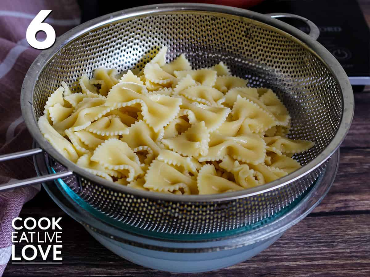 Bowtie pasta is in a strainer set over glass bowl