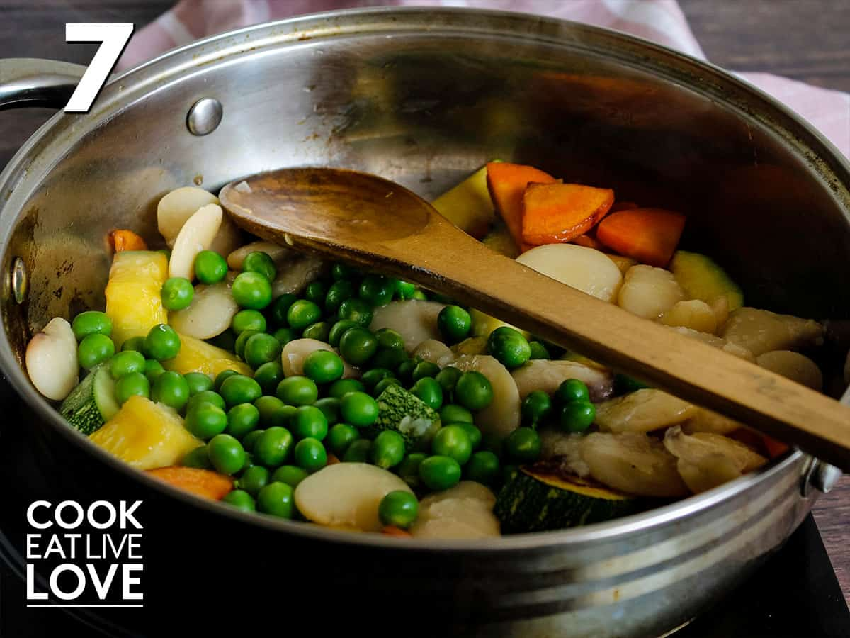 Coked zucchini and carrots in saute pan with peas