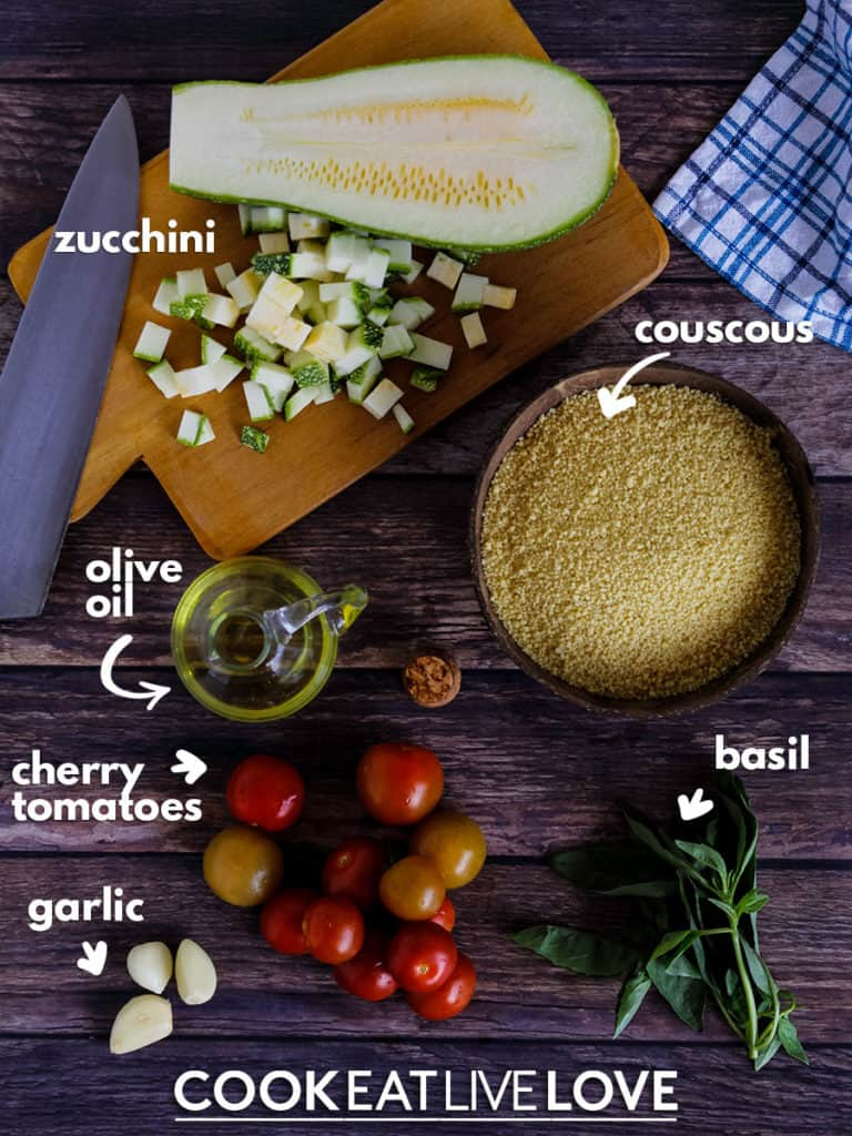 Overhead view of the ingredients used to make this healthy couscous recipe.  Zucchini, couscous, basil, tomatoes, garlic, olive oil.