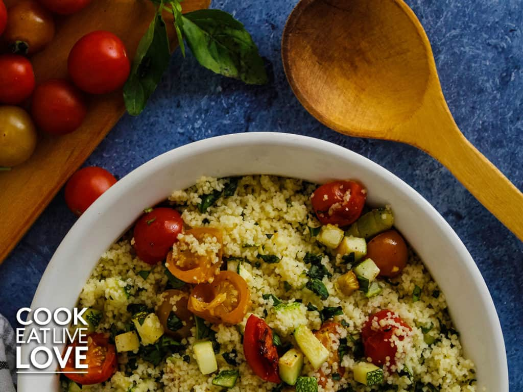 White serving bowl filled with couscous and tomato salad and wooden serving spoon