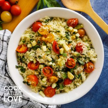 Overhead view of couscous with roasted zucchini and tomatoes in a white bowl, tightly cropped with a wooden spoon, whole tomatoes and fresh basil around the bowl