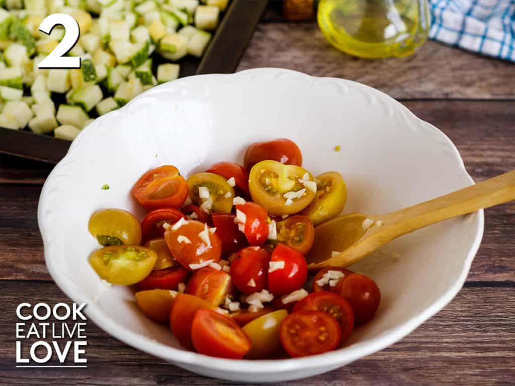 Tomatoes cut in half with olive oil and garlic in a white bowl. With wooden spoon in the bowl and the zucchini on the baking sheet in the top corner.