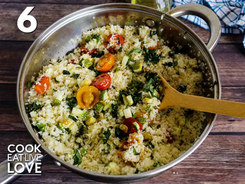 Pan of couscous with zucchini, tomatoes and basil.  Wooden spoon stirred up the couscous and is leaning against the edge of the pan.