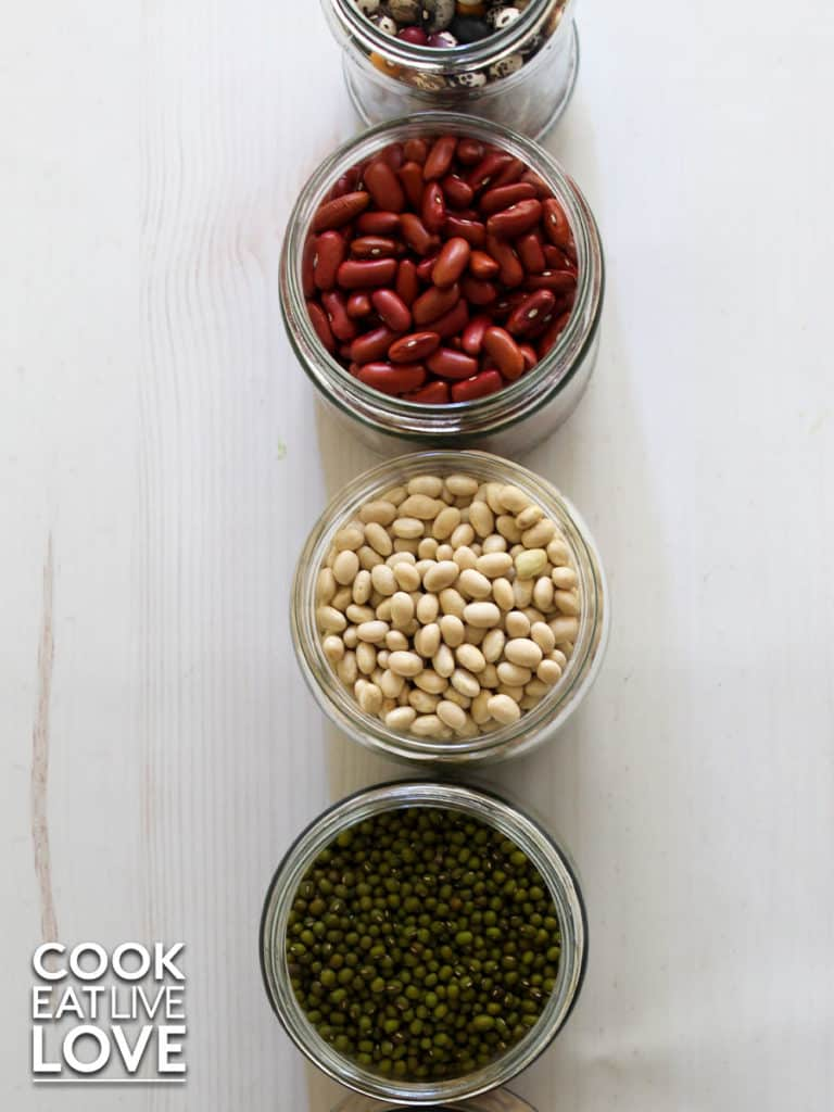 Overhead view of dried beans in jars in a row. Red beans, white beans and mung beans.