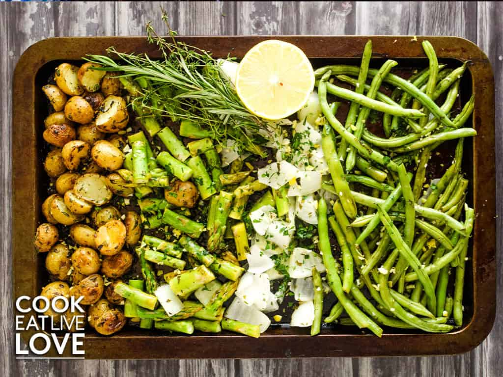 Overhead view of vegetables and potatoes on a sheet pan ready to place in the oven.