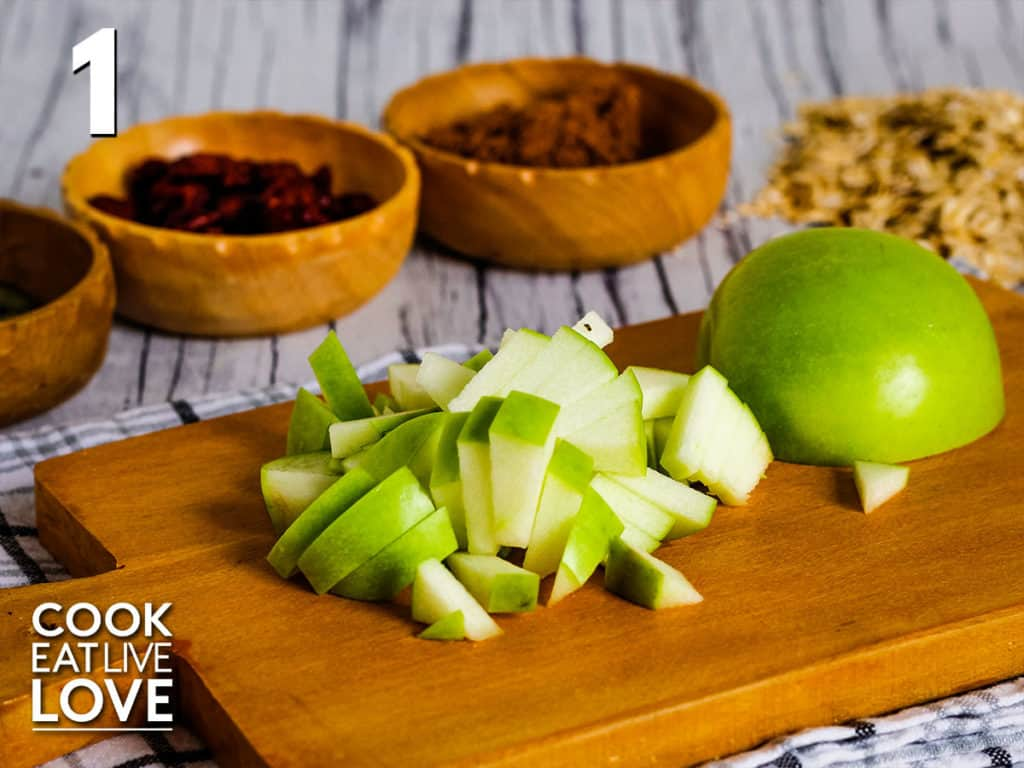 Chopped apple on a cutting board with other ingredients in the background to show the correct size of the apple.