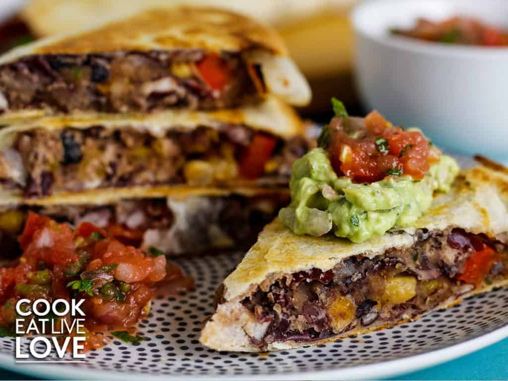 Refried bean vegan quesadillas ready to eat are stacked up on a gray and white polka dot plate.  One quesadilla triangle in the front is topped with guacamole and salsa .