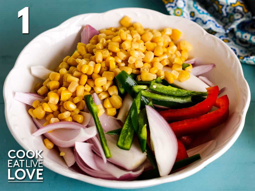 Corn, onions, bell pepper and jalapeno are combined in white bowl to get ready for the oven.