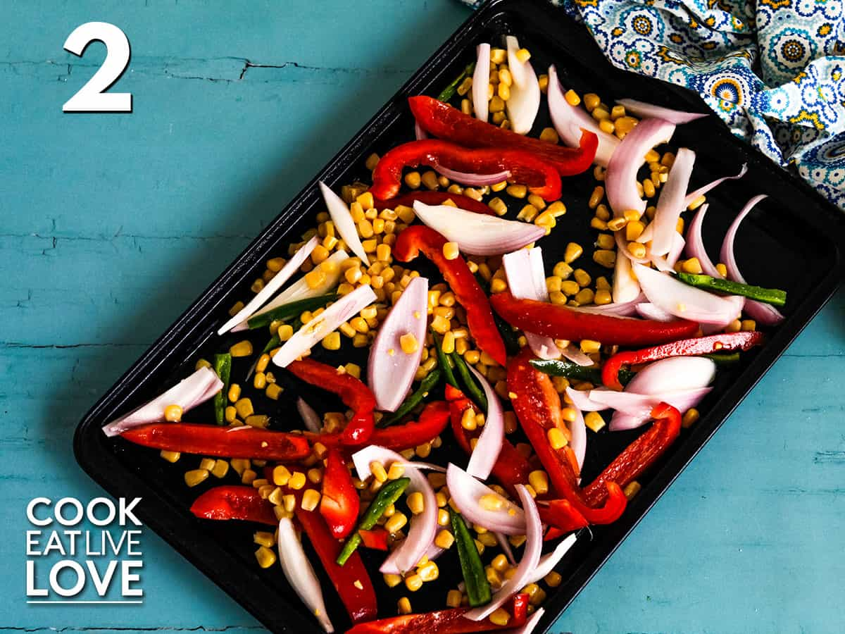 Veggies are now shown on a baking sheet ready for the oven.