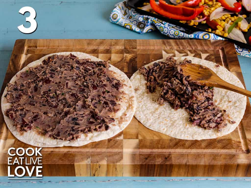 Two flour tortillas are laid on a cutting board beans are spread on one already and the other has beans on top with a spoon spreading them out. In the back are the veggies.