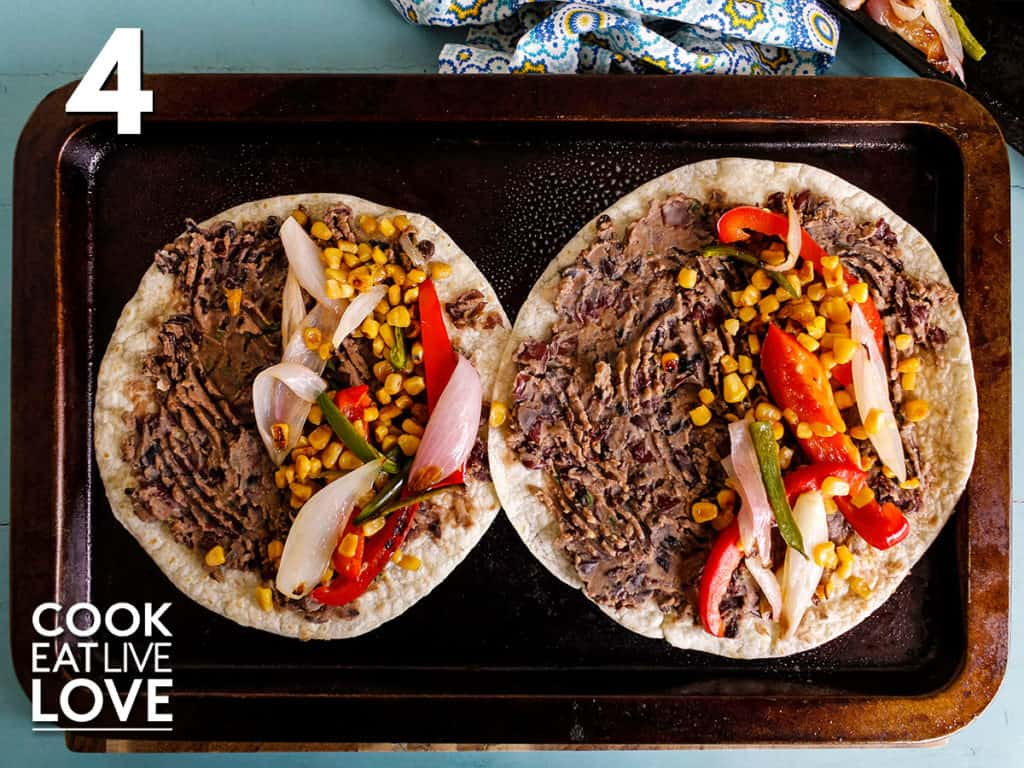 Tortillas are on a baking tray topped with beans over the entire surface and vegetables just on one half.
