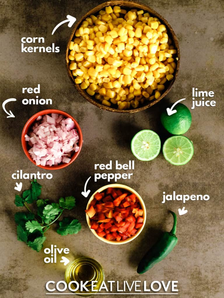 Overhead view of ingredients for roasted corn salsa:  corn kernels, limes, jalapeno, red bell pepper, olive oil, cilantro and red onion.