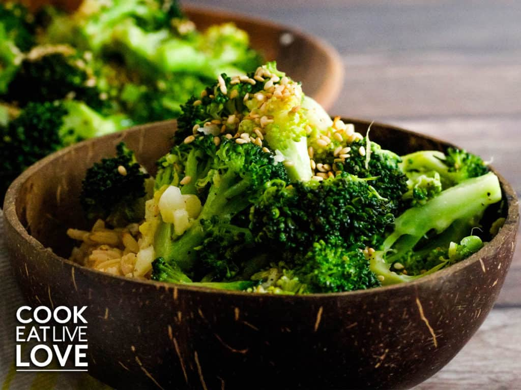 Dark brown bowl filled with cooked broccoli sprinkled with sesame seeds.  In the back is a plate of more sesame ginger broccoli.