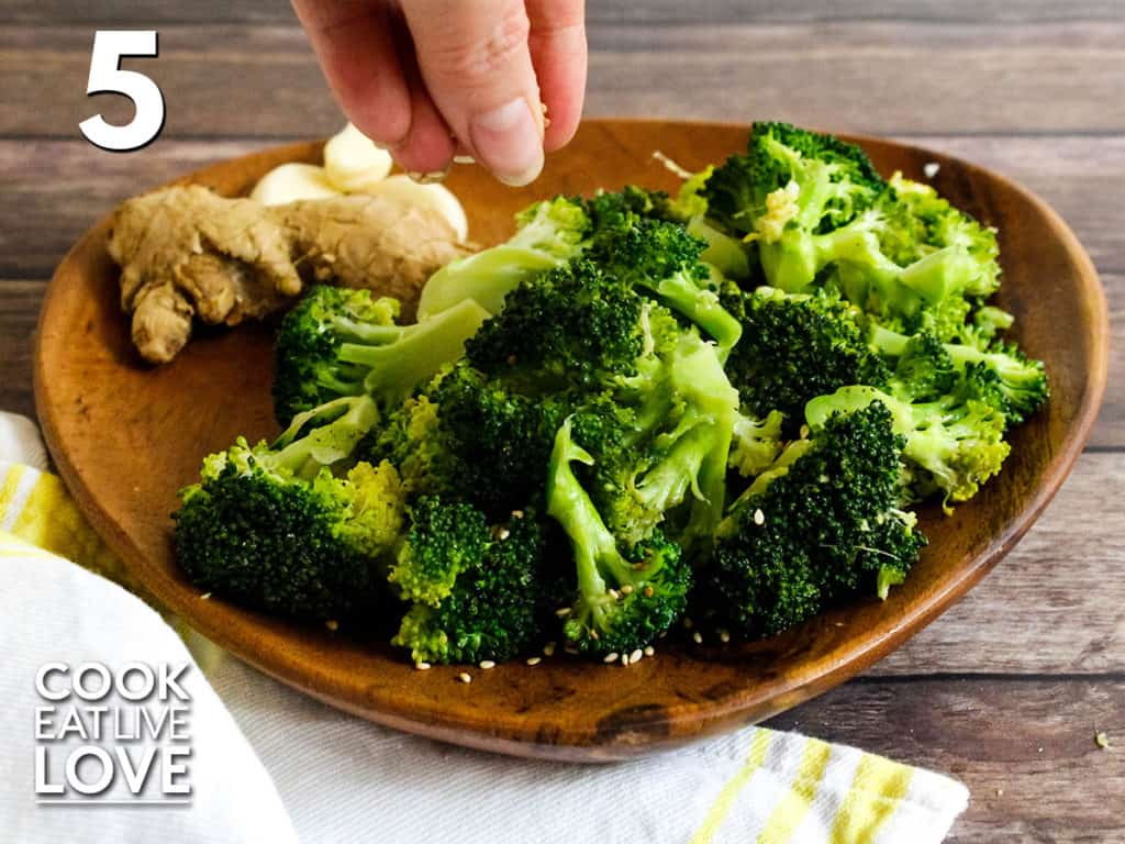 Broccoli is served up on a wooden plate, a hand sprinkling sesame seeds over the top.