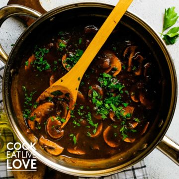 Mushroom sauce in skillet iwth wooden spoon