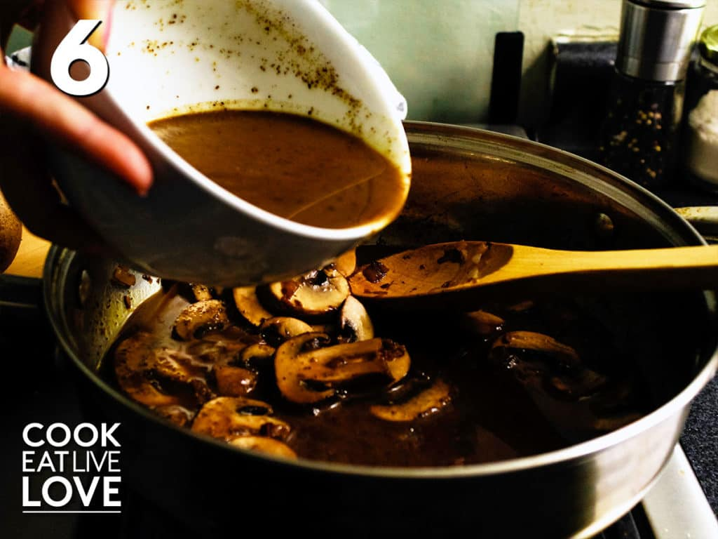 Skillet holds mushrooms, red wine and balsamic and a hand holds the bowl of cornstarch mushroom liquid pouring it into pan.