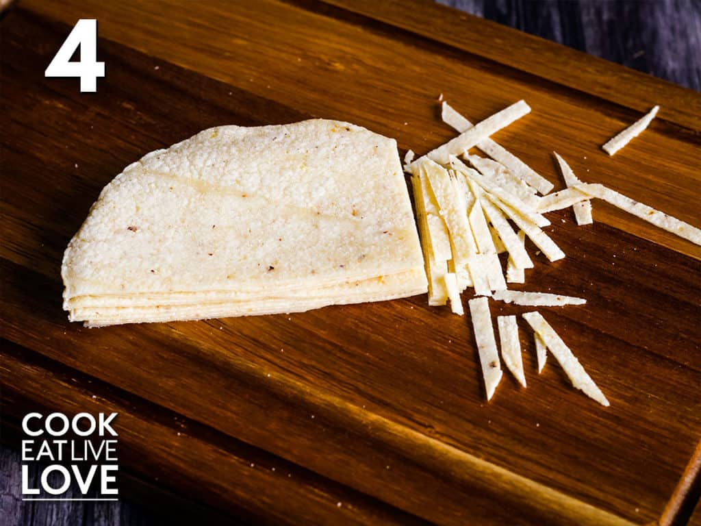 Corn tortillas are shown in a stack and cut in half and in the process of being cut into thin slices.