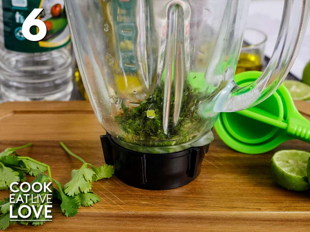 Front view of ingredients for the cilantro cumin vinaigrette in a blender.