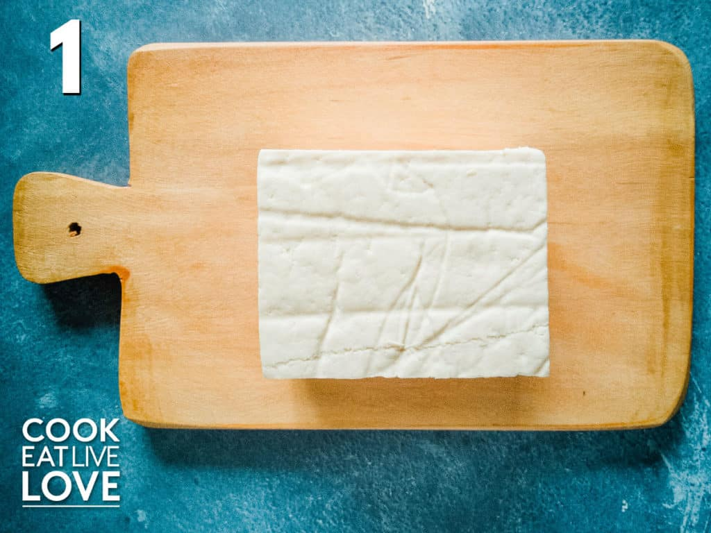 Block of tofu out of container and sitting on wooden cutting board on blue background.