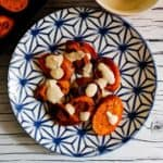 Overhead view of roasted carrots on a blue and white plate with tahini sauce on top. Plate on white and gray background.