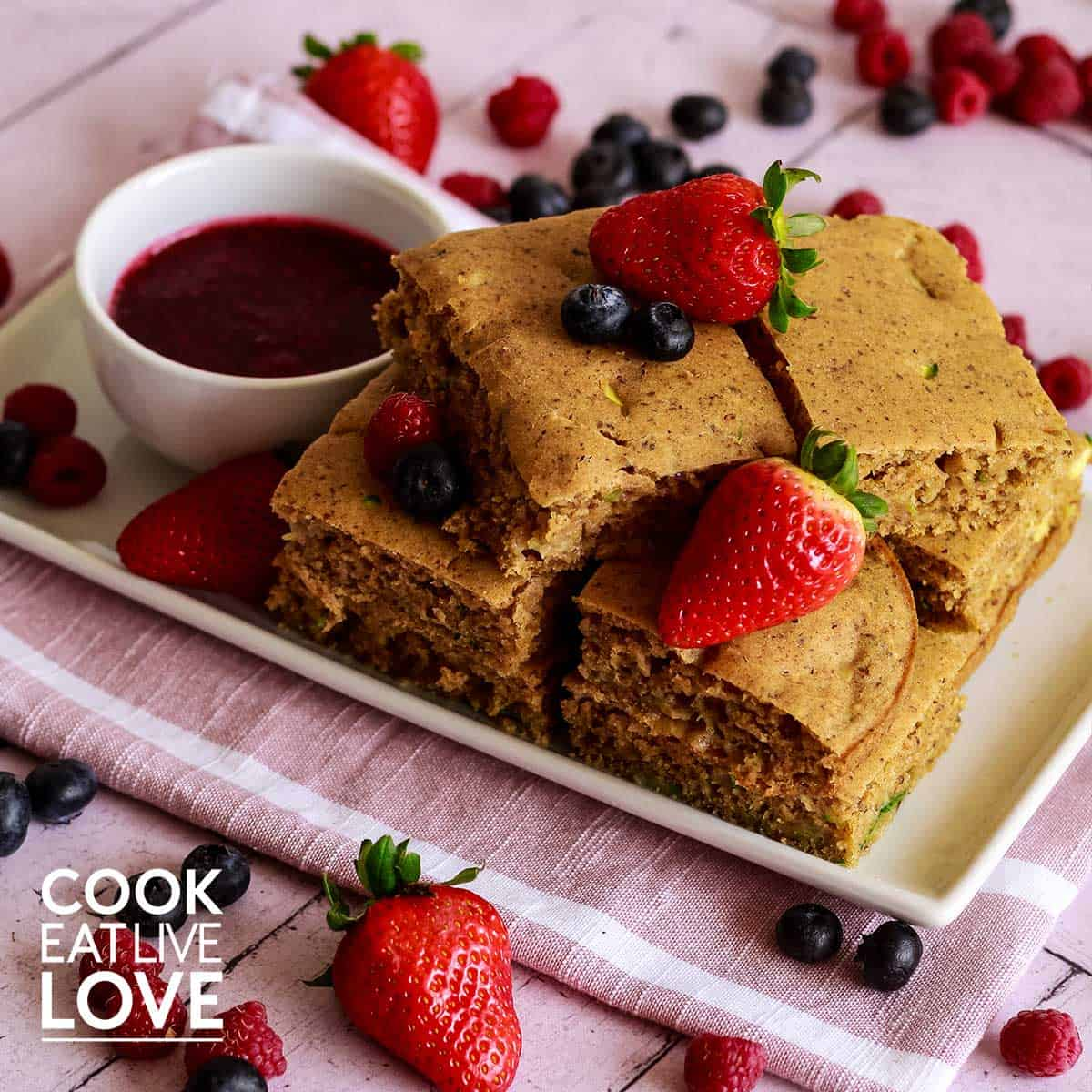 Squares of vegan sheet pan pancakes with berries stacked on a white rectangle plate.
