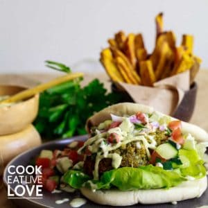 Front view of vegan falafel burger ready to eat with sweet potato fries in back.