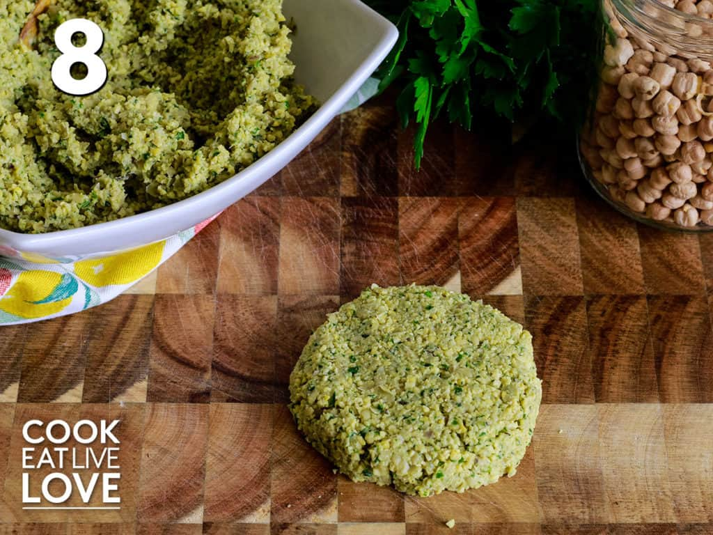 Falafel mixture from half cup measure is shaped into a patty laying on a cutting board.
