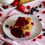 Vegan sheet pan pancakes on white and gray polka dot plate topped with mixed berry sauce and fresh berries.
