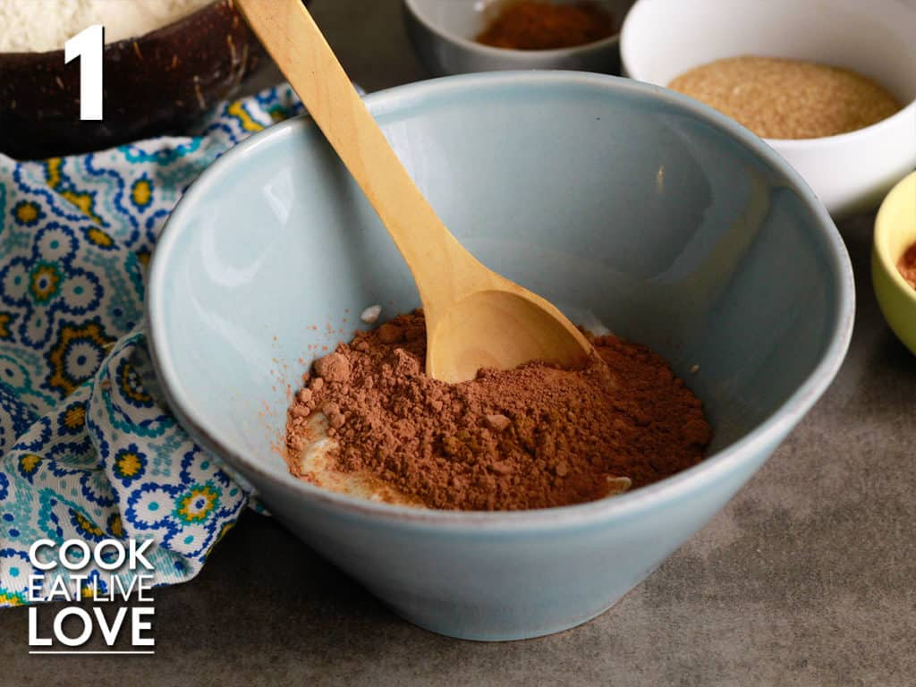 Yogurt, cacao powder, maple syrup and cinnamon in a small blue bowl with wooden spoon in the bowl. Behind bowl are other pancake ingredients.