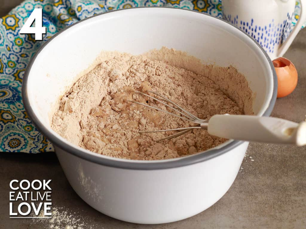 In a white bowl with gray trim, the wet and dry ingredients are mixed together with a whisk.