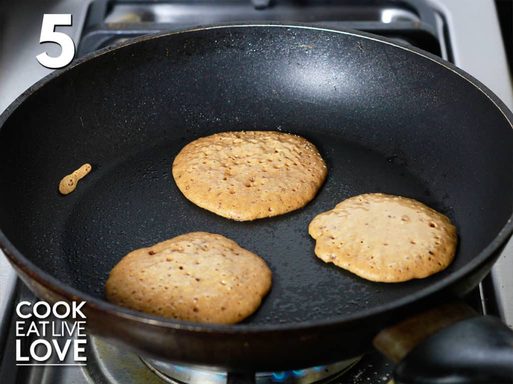 Three small pancakes poured into a pan showing the size of the mini pancakes.