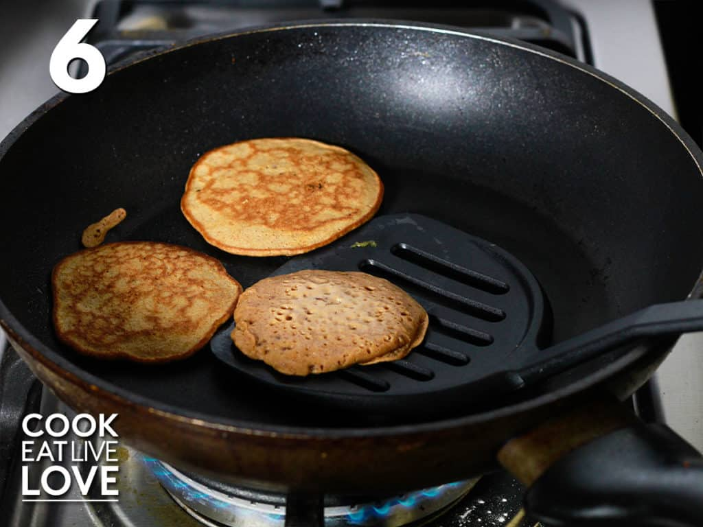 Spatula is under one pancake in the pan in order to flip it over to cook on the other side.  Other two pancakes in the pan are already flipped.