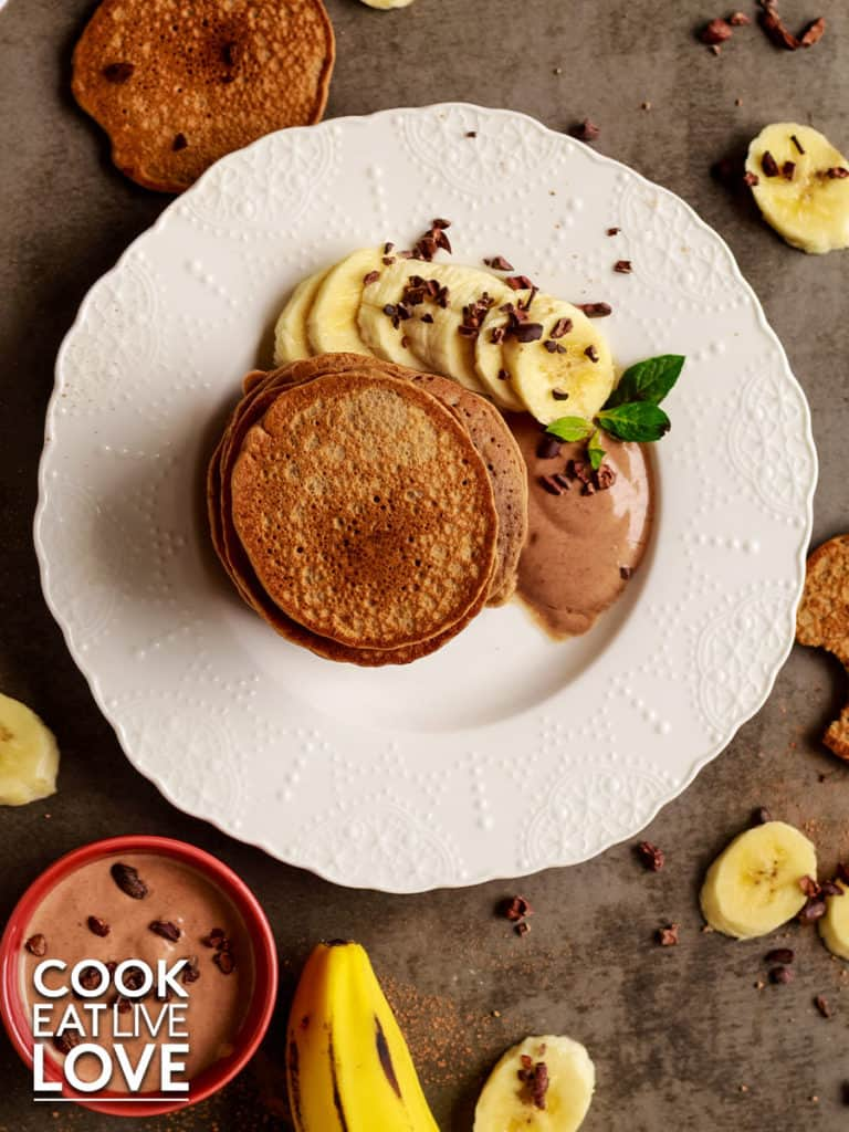 Overhead view of stack of chocolate protein pancakes with sliced bananas, cacao nibs and cacao yogurt on the side. On the gray background surrounding the plate are sliced bananas, cacao nibs, cacao yogurt in red bowl.