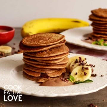 Front view of stack of 10 pancakes on a white plate with sliced bananas, cacao cream and fresh mint.