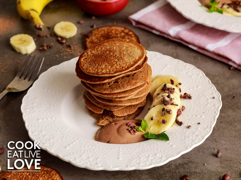 Front view of stack of chocolate protein pancakes on a white plate with cacao yogurt and sliced bananas.  On the dark gray surface around the plate are sliced bananas, cacao powder, and pancakes.