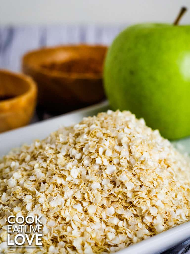 View of uncooked quinoa flakes on a plate with apple and small wooden bowls in the background.