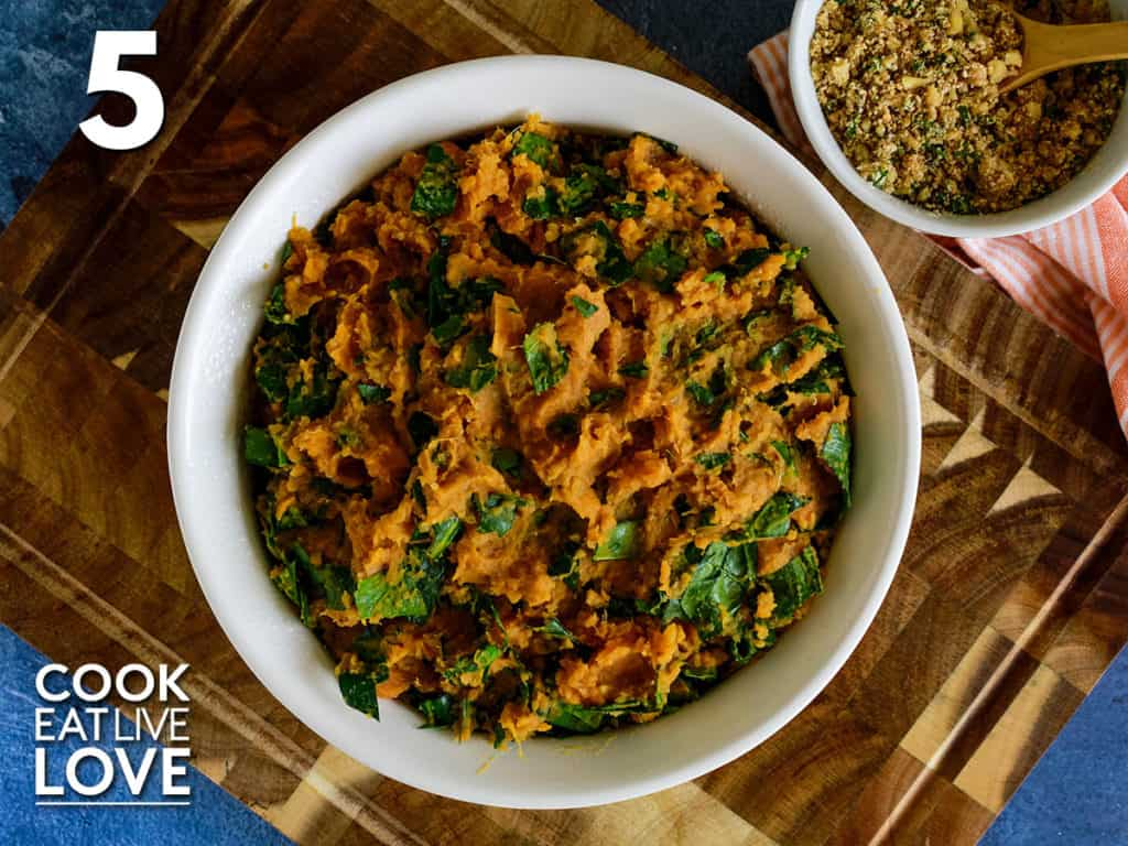 Mashed sweet potato, quinoa and spinach mixture are in a round casserole dish.
