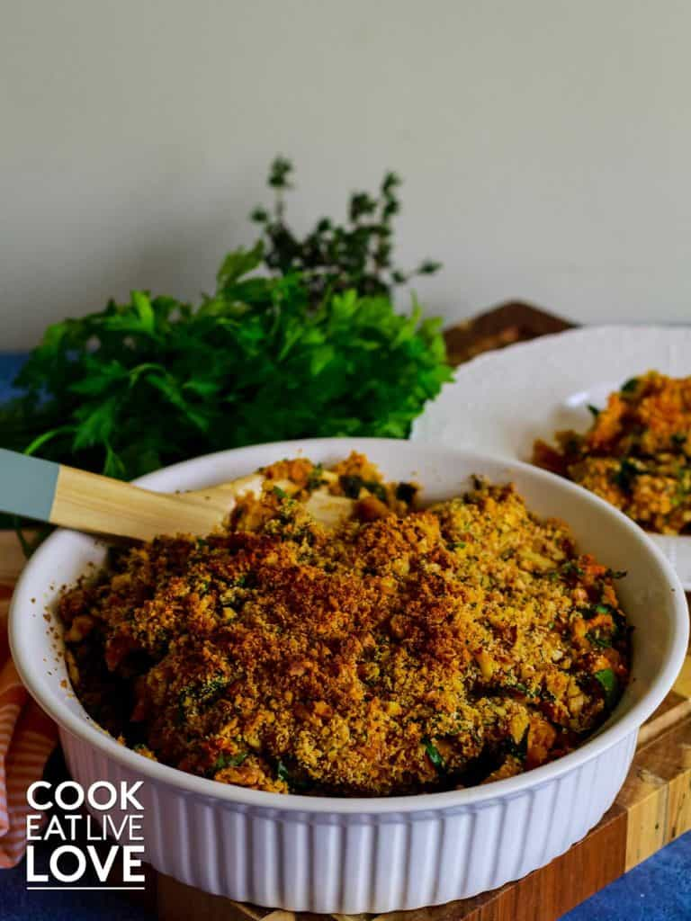 Round casserole dish of vegan sweet potato gratin with plate in background with a serving on it.