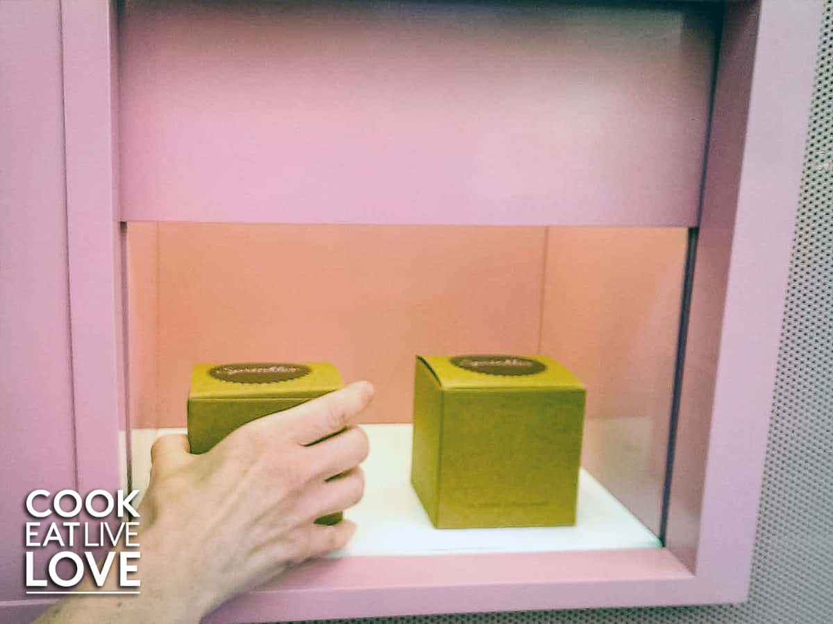 Hand reaching into grab boxed cupcake.
