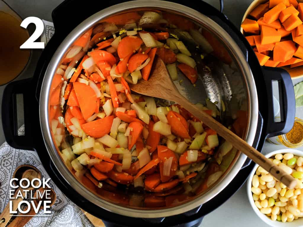 Vegetables in instant pot are cooked and ready for pumpkin and beans.